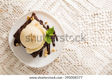 Chocolate brownie with vanilla ice cream, nuts and mint, served om white plate, copy space - stock photo