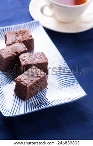 "Chocolate brownies on a vintage rectangular porcelain plate with traditional Japanese ""Jukusa"" pattern with blue stripes - stock photo"