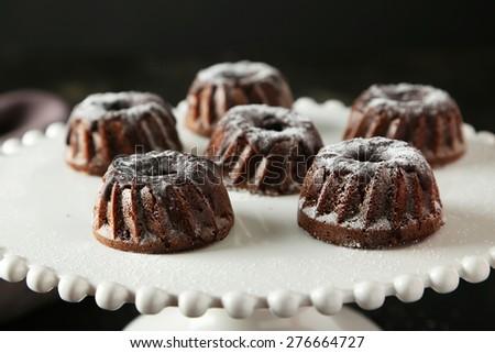 Chocolate bundt cakes on cake stand on black background - stock photo
