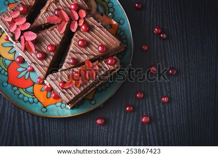 chocolate cake and ripe cranberries on a black wooden background. top view. holidays and events.  - stock photo