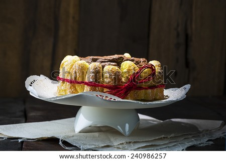 Chocolate cake decorated around the side with freshly baked crispy pastries and glazed with rich chocolate icing - stock photo