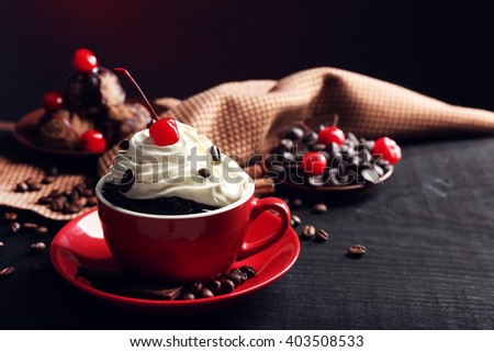 Chocolate cake in a red mug with a cherry on a dark background, close up - stock photo