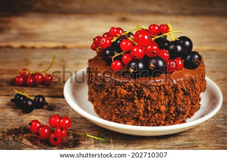 chocolate cake mini with red and black currants on a dark wood background. toning. selective focus on the currant on the cake - stock photo