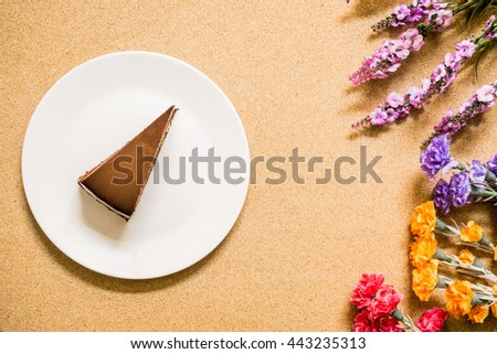 Chocolate cake on dish with flower, top view. - stock photo