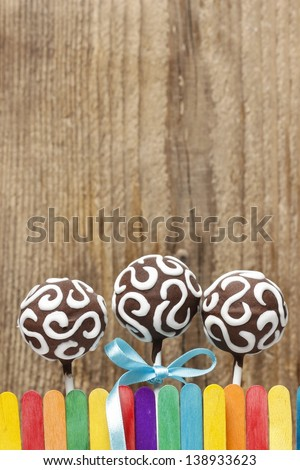 Chocolate cake pops on wooden background. Copy space. - stock photo