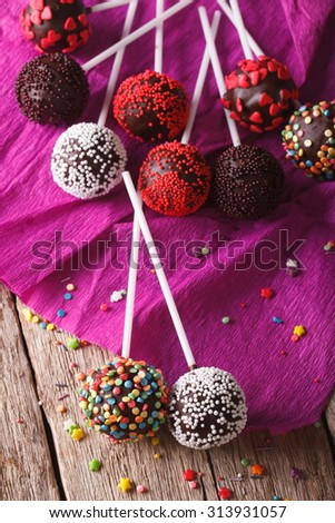 Chocolate cake pops with candy sprinkles close up on an old table. vertical - stock photo