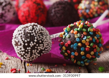 Chocolate cake pops with candy sprinkles macro on an old table. Horizontal