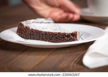 Chocolate Cake Slice on white dish and wooden background - stock photo
