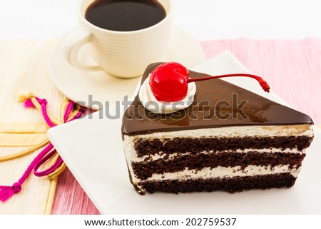 Chocolate cake slice with red cherry fruit and coffee cup .  - stock photo