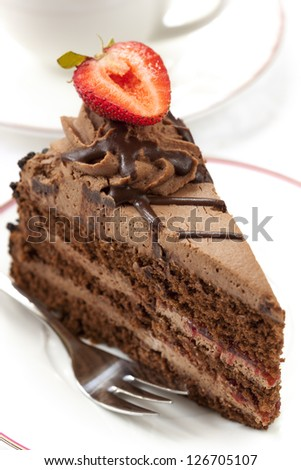 Chocolate cake topped with a strawberry, served with coffee. - stock photo