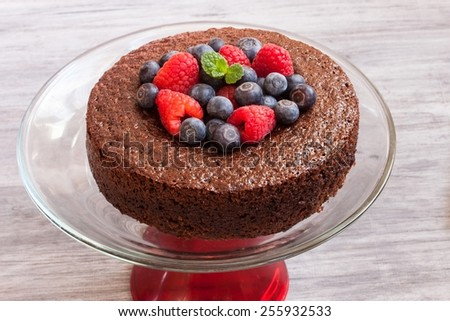 Chocolate cake topped with raspberries and blueberries - stock photo