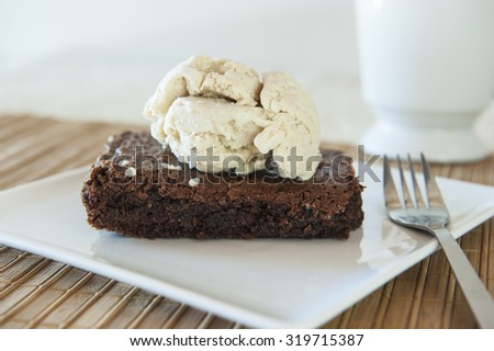Chocolate cake with a scoop of cinnamon ice cream on top on a white plate - stock photo