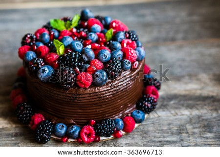 Chocolate cake with berries on wooden background - stock photo