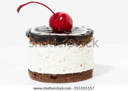 Chocolate cake with cherry on the top icing on the plate - stock photo