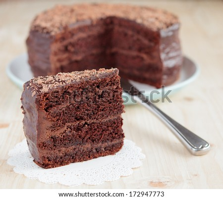 Chocolate cake with chocolate buttercream frosting and ganache, cut out, selective focus - stock photo