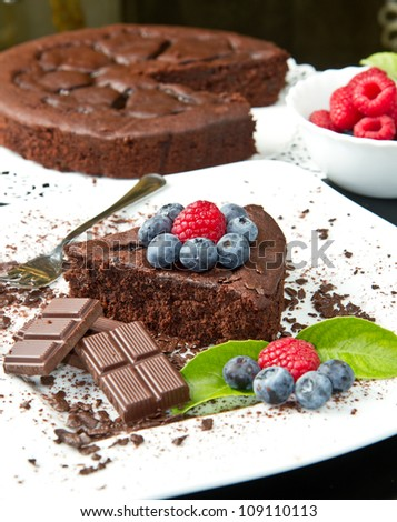 chocolate cake with fresh berry on white dish and black background - stock photo