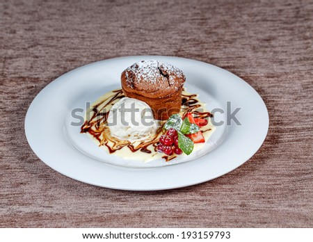 Chocolate cake with ice cream and fruit shot close-up on a table in a restaurant - stock photo