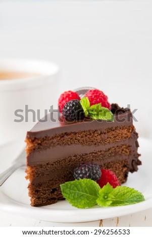 Chocolate cake with raspberry, blackberry, mint, white plate, tea, white wood background - stock photo
