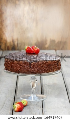 Chocolate cake with strawberries. Birthday party table, wooden background. Copy space, your text here - stock photo