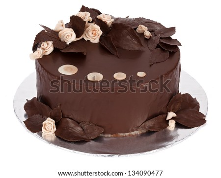 Chocolate cake with white marzipan and chocolate covered real plants decorations on round plate - stock photo