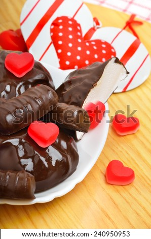 chocolate candies and a valentine heart on white plate on wooden background. - stock photo
