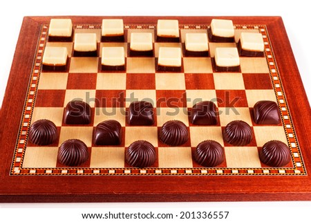Chocolate candies arranged as chess pieces on chess board - stock photo