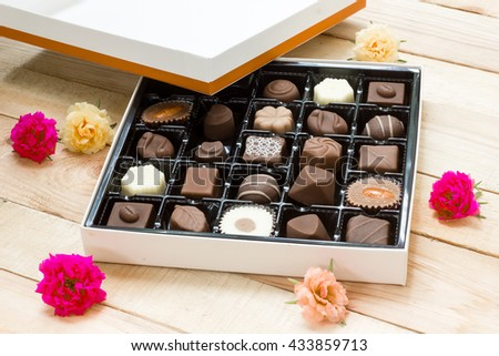 Chocolate candy in the box on wood background. - stock photo