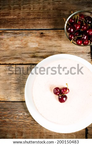 chocolate-cherry cheesecake on a dark wood background. toning. selective focus on the cherry on top of the cheesecake - stock photo