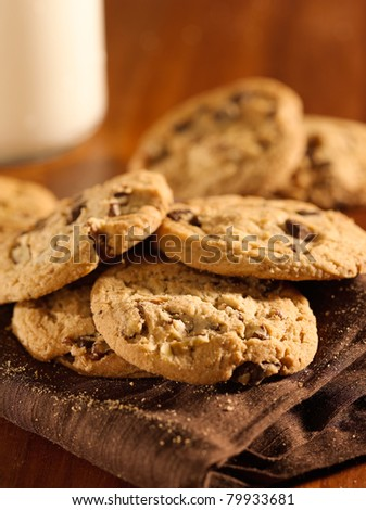 chocolate chip cookies and glass of milk in background - stock photo