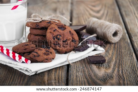 Chocolate chip cookies,chocolate and glass of milk on linen napkin on wooden background - stock photo