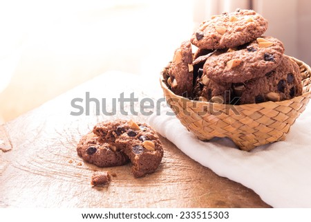 Chocolate chip cookies on napkin on wooden table. Stacked chocolate chip cookies close up - stock photo