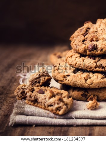 Chocolate chip cookies on natural linen napkin on wooden background with copy space.  Pile of chocolate chip cookies close up. - stock photo