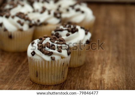 chocolate chip cupcakes on wooden kitchen table - stock photo