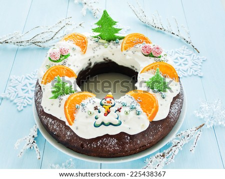 Chocolate Christmas cake with candies, tangerine and whipped cream. Shallow dof. - stock photo