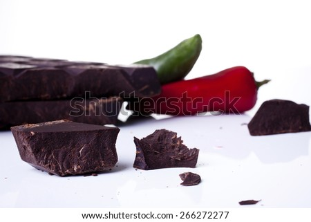 Chocolate chunks and chilies shot close up with shallow depth of field and on a white background - stock photo