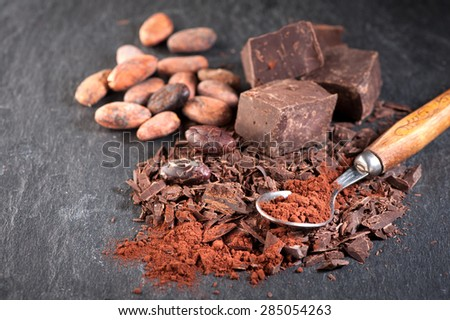 Chocolate, cocoa beans and cocoa powder on a stone background - stock photo