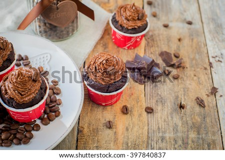 Chocolate coffee cupcakes muffins on a plate with coffee beans. Wooden background - stock photo