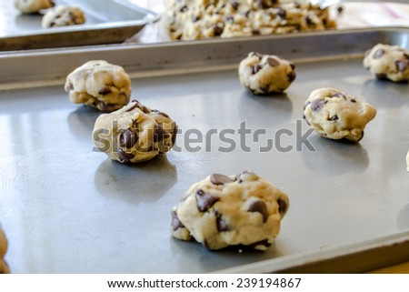 Chocolate cookie dough balls sitting on baking pan ready to be placed in oven to bake - stock photo