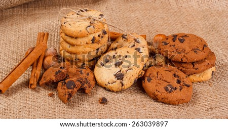 Chocolate cookies, hazelnut, cinnamon. Chocolate cookies with hazelnut cinnamon on the wooden table. chocolates, hazelnuts, cinnamon rolls in a row on white wooden table background. christmas cookies - stock photo