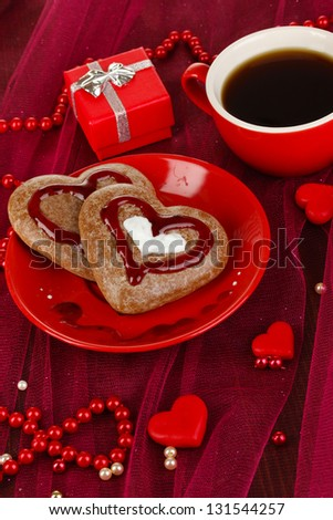 Chocolate cookies in form of heart with cup of coffee on pink tablecloth close-up - stock photo