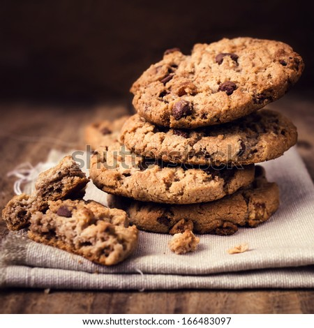 Chocolate cookies on white linen napkin on wooden table. Chocolate chip cookies in rustic style close up. - stock photo