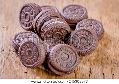 Chocolate cookies with cream on wooden table - stock photo