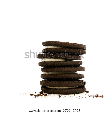 Chocolate cookies with creme filling and crumbs on white background - stock photo