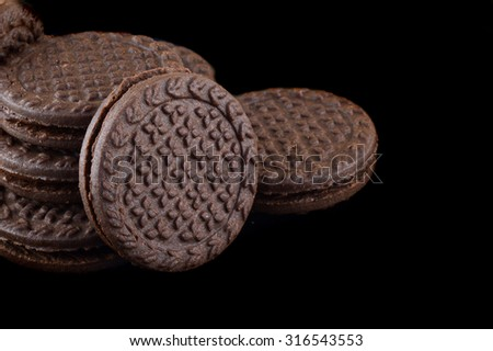 Chocolate cream cookies. brown chocolate sandwich biscuits with cream filling on black background.   - stock photo