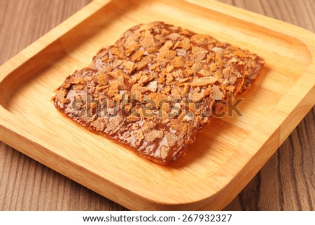 Chocolate crunch on wooden plate - stock photo