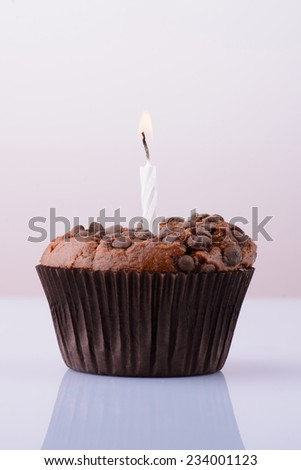 chocolate cupcake with a candle on a white background. birthday - stock photo