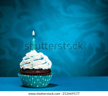 Chocolate Cupcake with  icing and lit birthday candle over a blue background - stock photo