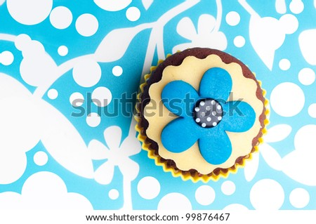 chocolate cupcake with yellow and aqua blue flower on top - stock photo