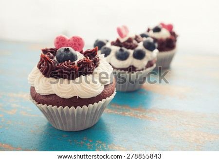 Chocolate Cupcakes in a Row Decorated with Icing, Blueberries and Heart Shaped Candies for Valentines Day, on Rustic Blue Table Top Surface - stock photo