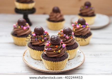 Chocolate cupcakes in golden foil with chocolate frosting, colorful sprinkles and chocolate ball on the top - stock photo